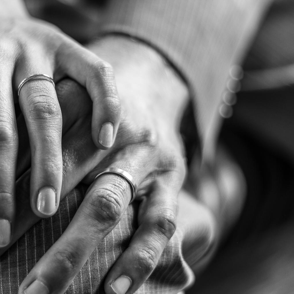 mains des époux portant leurs alliances