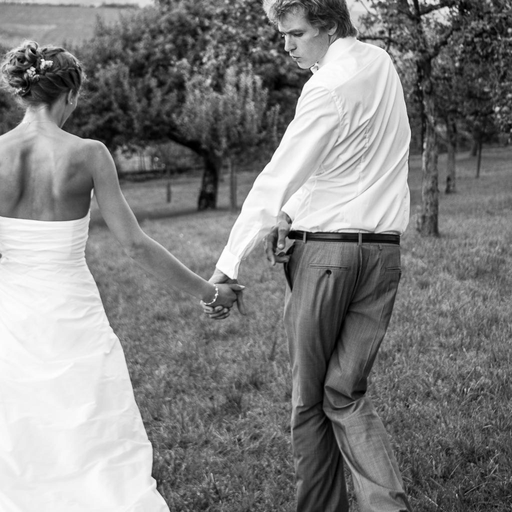 époux se tenant par la main dans la campagne