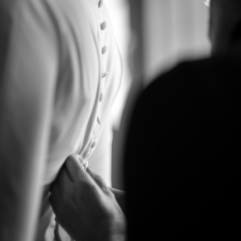 mains boutonnant le corsage de la mariée