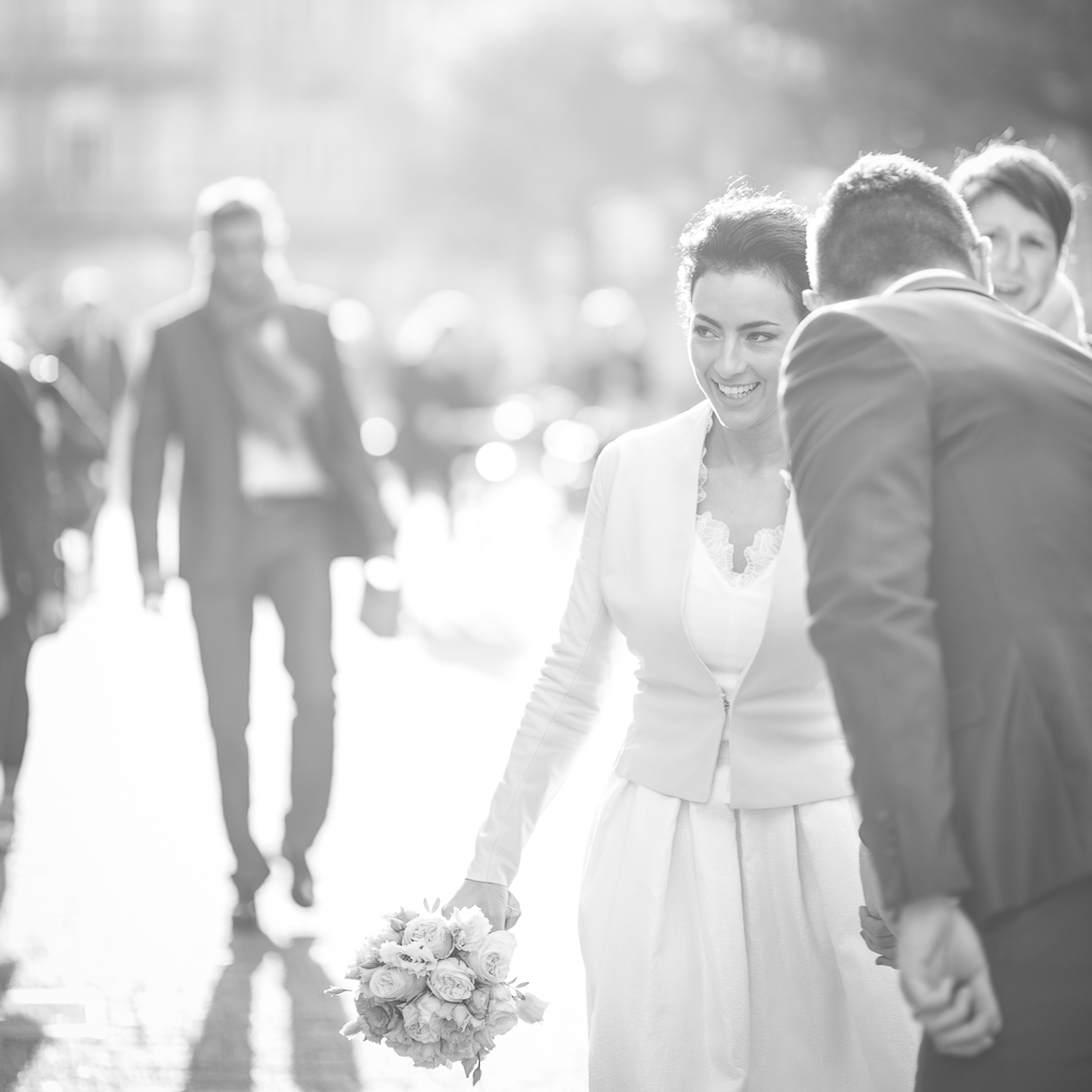 époux glissant quelques mots à l'oreille de sa femme portant son bouquet et souriant