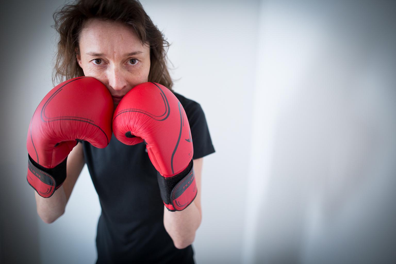 femme en garde, aux gants de boxe rouges